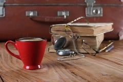 Tasse Kaffee, Weinlesekoffer, Uhren, Gläser und alte Bücher Stockbild