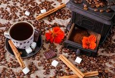 Tasse Kaffee wird auf altem Eisenwerk mit Schokolade, Zucker, Zimtbohnen getan Stockfotos