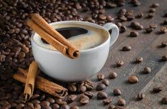 Tasse Kaffee, Zimtstangen, Kaffeebohnen lizenzfreie stockbilder