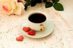 Tasse Kaffee, Zuckerherzen und ein Blumenstrauß von Sahnerosen Stockfoto