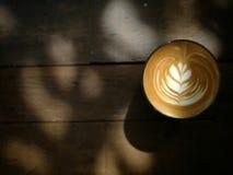 Tasse Kaffee, zum auf den Holztisch mit heißer Lattekunst zu gehen Abbildung der roten Lilie Beschneidungspfad eingeschlossen Lizenzfreie Stockbilder