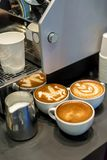 Tasse Kaffees mit schöner Lattekunst auf grauer Tabelle Stockfoto