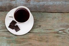 Tasse Kaffees mit Schokolade auf Holztisch mit Kopienraum Lizenzfreie Stockfotos