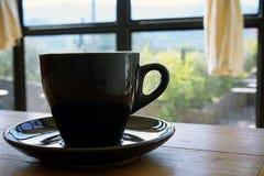 Tasse noire avec cuire le café à la vapeur chaud sur la table en bois avec le fond vert brouillé de jardin image libre de droits