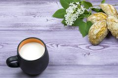 Tasse noire avec du lait Biscuits doux faits maison Brin et fleurs lilas blanches sur la table Image stock