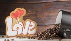 Tasse noire avec les graines de café, biscuits sous forme d'amour de mot et deux coeurs rouges, sur un fond en bois Photo stock