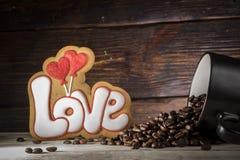 Tasse noire avec les graines de café, biscuits sous forme d'amour de mot et deux coeurs rouges, sur un fond en bois Photographie stock libre de droits