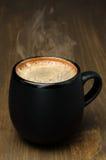 Tasse noire de café avec la mousse sur une table en bois Image libre de droits