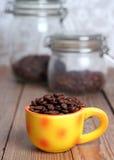 Tasse orange avec des grains de café Photo libre de droits