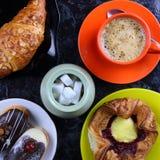 Tasse orange avec du café, le gâteau et un croissant Photo stock