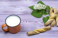 Tasse orange avec du lait Biscuits doux faits maison Brin et fleurs lilas blanches sur la table Photos libres de droits