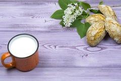 Tasse orange avec du lait Biscuits doux faits maison Brin et fleurs lilas blanches sur la table Photos stock