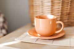Tasse orange sur la table en bois avec la serviette en osier avec la lumière du soleil Photographie stock libre de droits