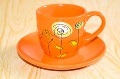 Tasse orange sur une soucoupe Photos libres de droits