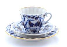 Tasse, plat et soucoupe de porcelaine sur un fond blanc Images libres de droits