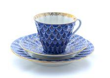 Tasse, plat et soucoupe de porcelaine sur un fond blanc Images stock