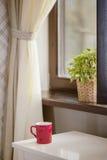 Tasse pour le café contre une fenêtre Images stock