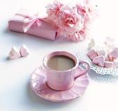 Tasse rose avec du café, les coeurs de guimauves, le cadeau et le bouquet des roses roses Photos libres de droits