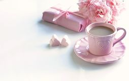 Tasse rose avec du café, les coeurs de guimauves, le cadeau et le bouquet des roses roses Photographie stock libre de droits