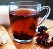 Tasse rose de chien de thé avec la sucrerie sur la table Images stock