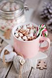Tasse rose de chocolat chaud avec des guimauves sur la table photo stock