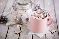 Tasse rose de chocolat chaud avec des guimauves sur la table photos stock