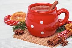 Tasse rouge avec du chocolat chaud et la cannelle Photographie stock libre de droits