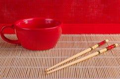 Tasse rouge, bâtons en bambou pour des sushi Images stock