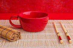 Tasse rouge, baguettes, une serviette en bambou Images libres de droits