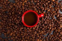 Tasse rouge d'expresso, café avec des grains de café autour Photo stock