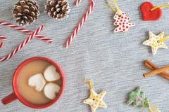 Tasse rouge de cacao chaud avec le cadre des ornements faits main de Noël, cannes de sucrerie, pinecones photos stock