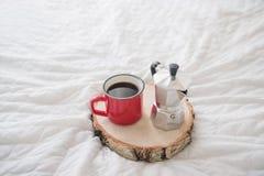 Tasse rouge de café avec le fabricant de café sur le plateau en bois sur le lit blanc Photos libres de droits