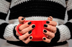 Tasse rouge de thé dans des ses mains Photographie stock libre de droits