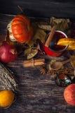 Tasse rouge de vin chaud chaud en automne parmi des feuilles Images libres de droits
