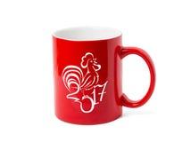 Tasse rouge et un dessin stylisé d'un coq Photographie stock libre de droits