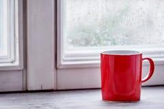 Tasse rouge sur le filon-couche lumineux de fenêtre de matin Photographie stock libre de droits