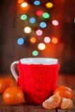 Tasse rouge tricotée avec des lumières de Noël au fond Photos stock