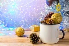 Tasse rustique d'émail avec des décorations de Noël au-dessus de beau fond de bokeh Photos stock