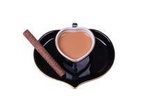 Tasse sous forme de coeur de café avec du lait et des biscuits sur le blanc Image libre de droits