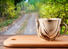 Tasse sur une surface en bois sur un fond d'un chemin forestier avec des arbres photos libres de droits