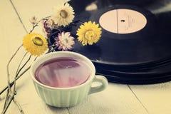 Tasse Tee, alte Vinylaufzeichnungen und trockene Blumen Lizenzfreie Stockbilder