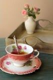 Tasse Tee auf einem Hintergrund von Blumen in einem Vase Lizenzfreies Stockfoto