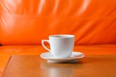 Tasse Tee auf hölzerner Tabelle mit orange Hintergrund Lizenzfreie Stockfotos