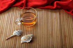 Tasse Tee auf Holztisch-Matte mit Muscheln Stockfotos