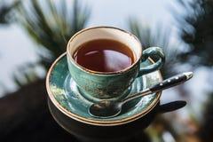 Tasse Tee in BeautifulHandmade-Tasse und Untertasse auf dem Glastisch mit Reflexion von Palmen Lizenzfreies Stockbild