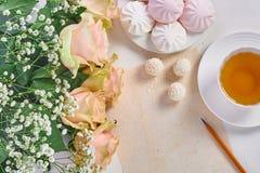 Tasse Tee, Blumenstrauß von Rosen und Bonbons stockfotos