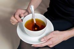 Tasse Tee an den Händen einer Frau Stockfotografie