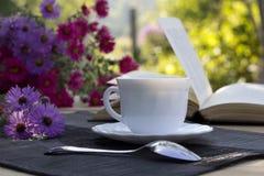 Tasse Tee, ein Blumenstrauß von Blumen und ein Buch Stockfoto
