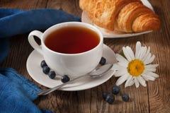 Tasse Tee Hörnchen und Blume stockfotos