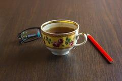 Tasse Tee, Handy, Bleistift, Gläser auf dem hölzernen Bürodesktop Stockfoto